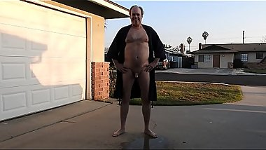 A daddy in a robe peeing in front of the neighbors.