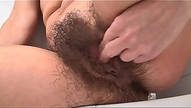 Hairy woman Eva soaps up her thick pussy hair